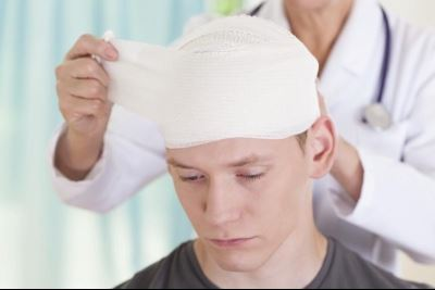 Doctor removing head bandage